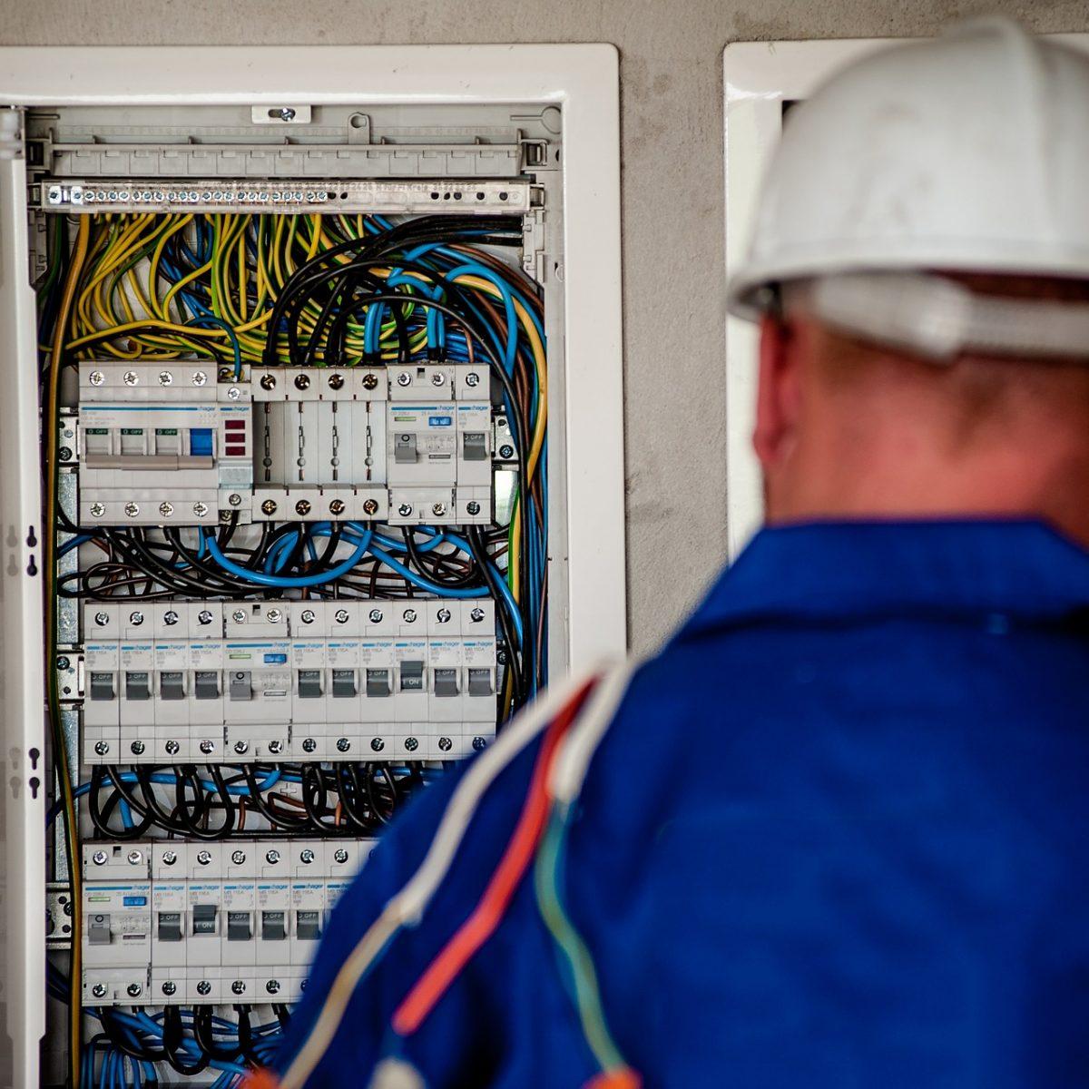 Techniker vor einem geöffneten Schaltschrank
