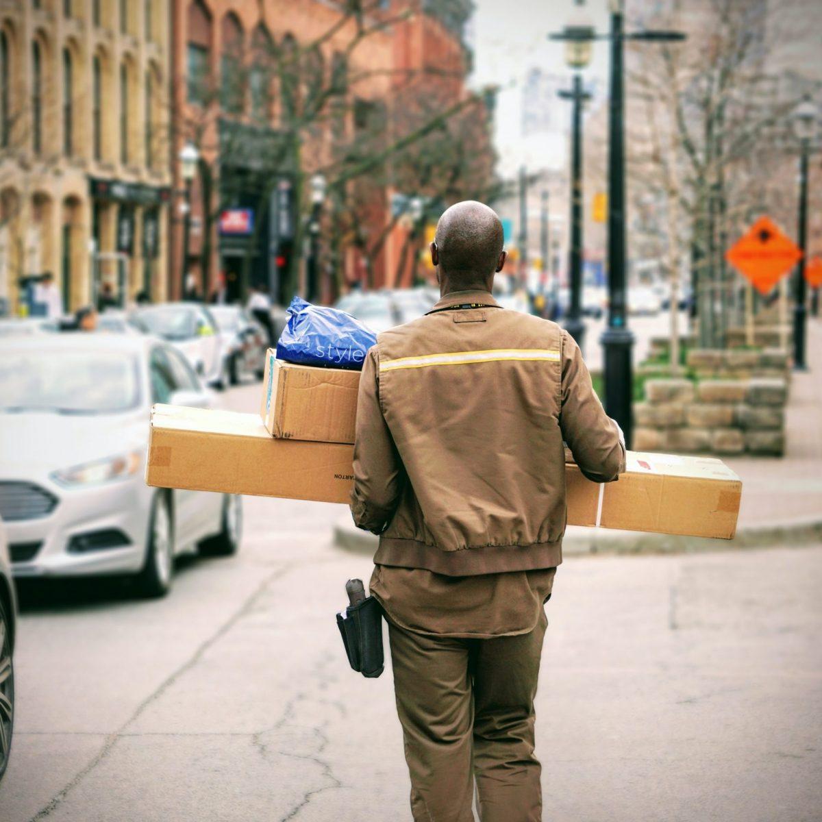 Paketbote trägt mehrere Pakete über die Straße