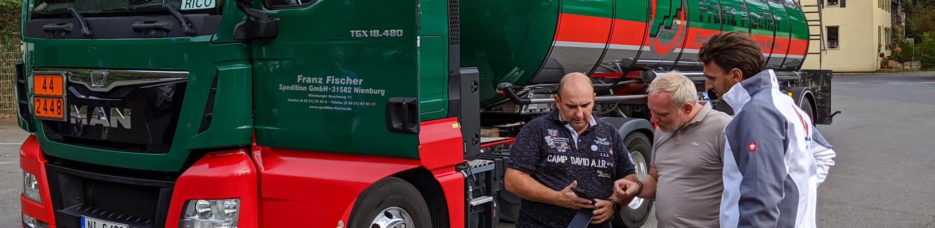 Drei Personen stehen vor einem LKW und schauen auf ein Smartphone